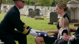 Kelly, excepting the flag from the coffin.