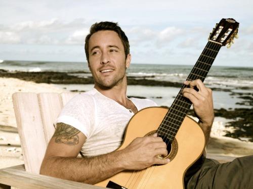 Alex O'Loughlin playing the guitar