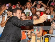 """WAIKIKI, HI - SEPTEMBER 19: Alex OLoughlin takes a selfie with a fan before attending the Sunset On The Beach event celebrating the 10th season of """"Hawaii Five-0"""" and season 2 of """"Magnum P.I."""" at Queen's Surf Beach on September 19, 2019 in Waikiki, Hawaii. (Photo by Darryl Oumi/Getty Images)"""